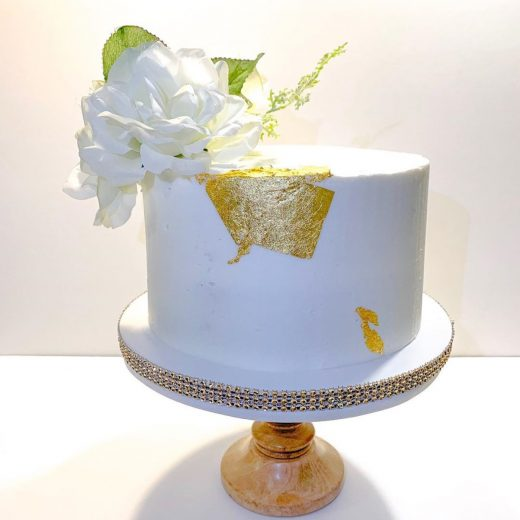 Brilliant White an Gold Wedding Cake with large white blossom on wooden cake stand